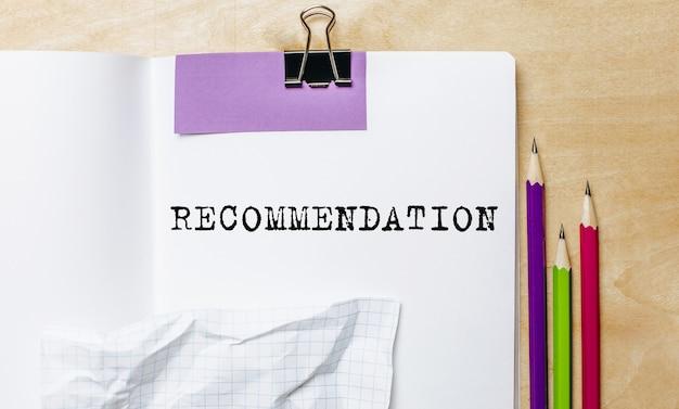 Raccomandazione testo scritto su carta con matite sulla scrivania in ufficio