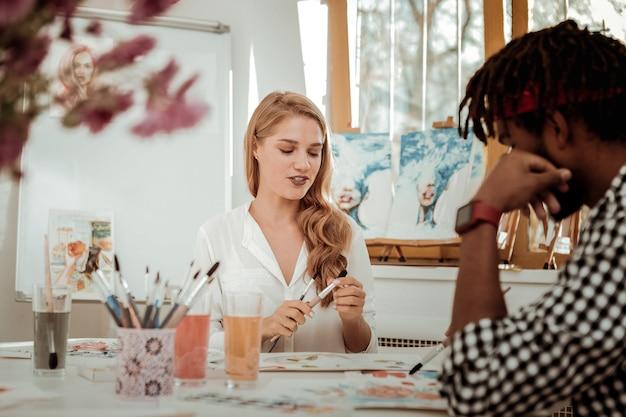Raccomandare il pennello. artista di talento dai capelli biondi che consiglia un buon pennello da pittura al suo collega