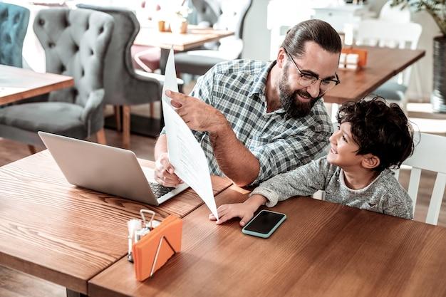 Consigliare il piatto. padre barbuto con gli occhiali che consiglia alcuni piatti il suo piccolo figlio