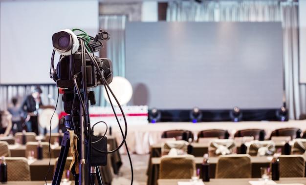 Riunione del seminario di registrazione video cameraman che sale sul palco presenta lo schermo nella sala conferenze, il concetto di produzione di eventi e seminari