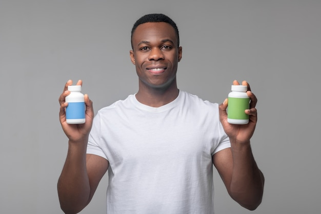 Recupero. gioioso attraente uomo dalla pelle scura che tiene mostrando confezioni di vitamine in mani in piedi in studio
