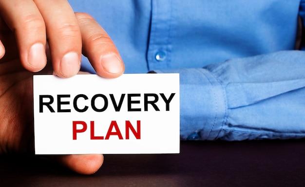 Piano di recupero è scritto su un biglietto da visita bianco nella mano di un uomo. concetto di pubblicità