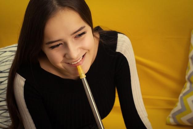 Ricreazione e intrattenimento. la giovane bella ragazza fuma un narghilè in un bar, si diverte con gli amici, sorride, beve