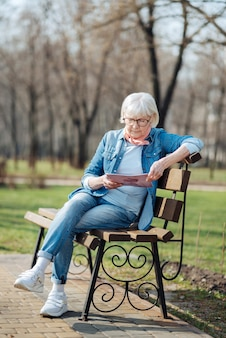 Ricreativo. determinata donna bionda leggendo una rivista mentre era seduto in panchina