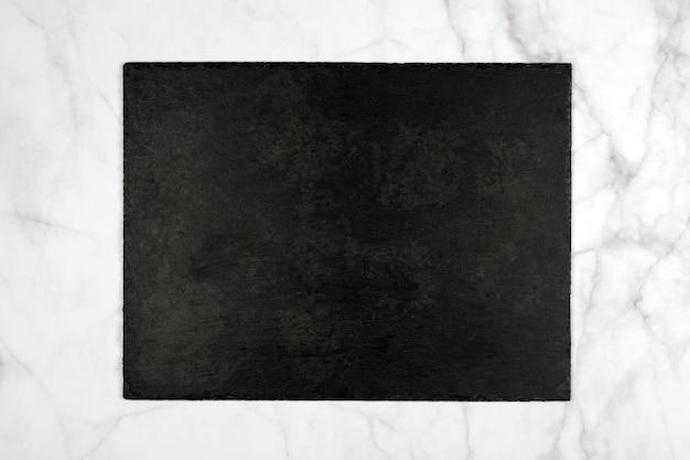 Tagliere in pietra ardesia nera rettangolare, cartello vuoto su marmo chiaro.