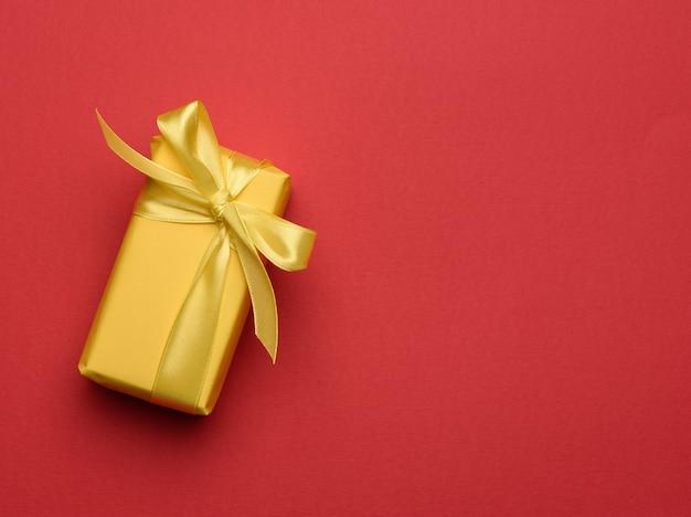 Scatola rettangolare con un regalo avvolto in carta gialla e legato con un nastro di seta giallo, vista dall'alto