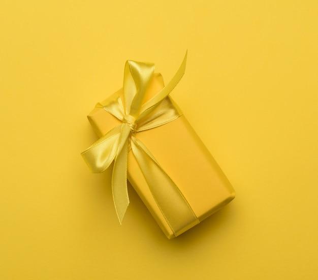 Scatola rettangolare con un regalo avvolto in carta gialla e legato con un nastro di seta gialla