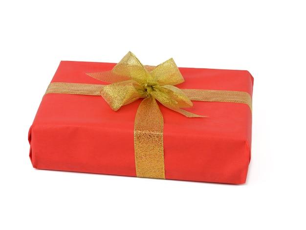 Scatola rettangolare avvolta in carta rossa e legata con un nastro dorato su sfondo bianco, celebrazione