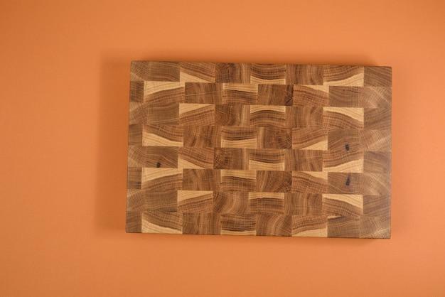 Tagliere da cucina di taglio marrone in legno vuoto rettangolare su sfondo arancione, vista dall'alto