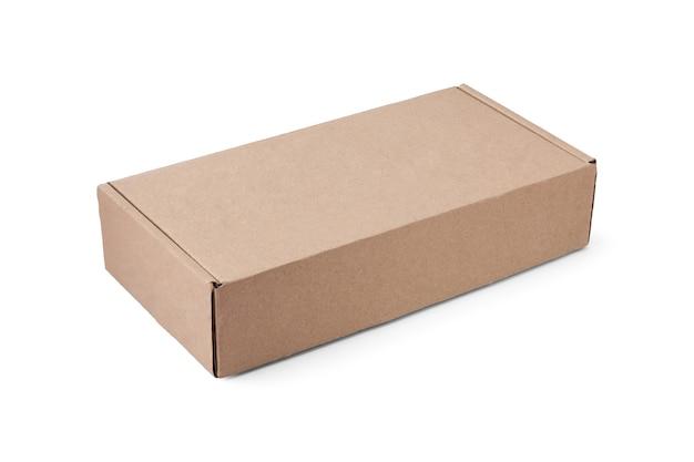 La scatola di cartone piatta rettangolare per l'imballaggio di pacchi o regali giace orizzontalmente ad angolo, isolata su bianco.