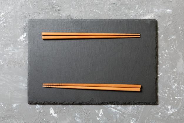 Piatto rettangolare in ardesia con bacchette per sushi su superficie in marmo nero