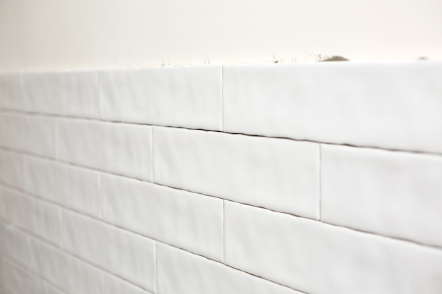 Piastrella rettangolare in ceramica bianca sulla parete della cucina. riparazioni in cucina. piastrelle in ceramica bianca alla moda alla moda. ristrutturazione appartamenti e bagni.