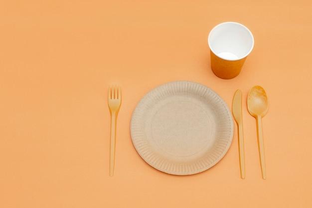 Forchetta, cucchiaio, coltello, piatto e tazza riciclabili su fondo beige. utensili da cucina. vista dall'alto. stile minimalista. copia spazio