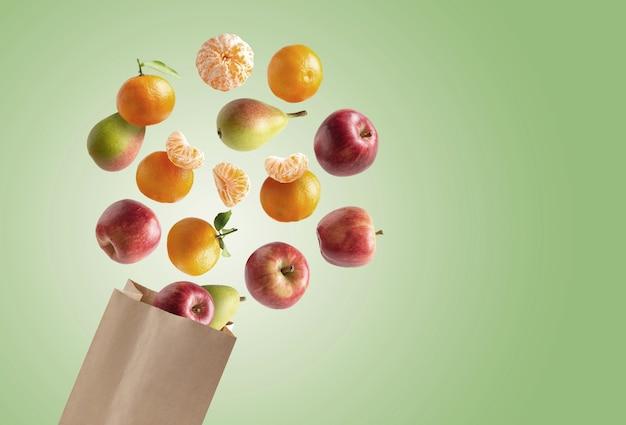 Sacco di carta riciclabile con frutta fresca che vola fuori