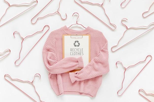 Riciclare il concetto di vestiti. maglione lavorato a maglia rosa pallido con appunti su sfondo bianco. vestiti autunnali e invernali.