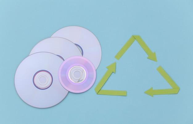 Segno di frecce riciclate e dischi cd su sfondo blu. vista dall'alto