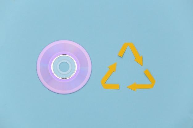 Segno di frecce riciclato e disco cd su sfondo blu. vista dall'alto