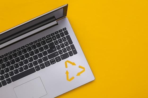 Segno riciclato delle frecce e tastiera del computer portatile su fondo giallo. vista dall'alto