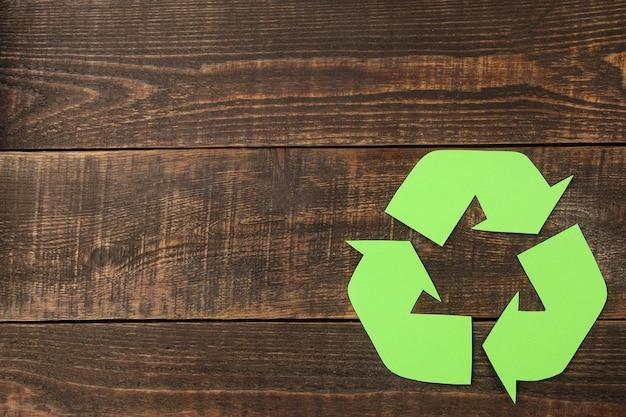 Segno di riciclaggio su un tavolo di legno marrone. vista dall'alto. concetto di eco