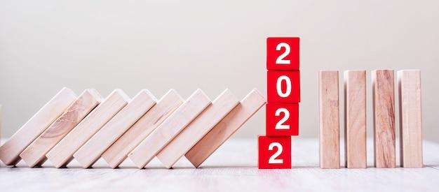 I blocchi cubici rossi 2022 smettono di cadere blocchi sul tavolo. affari, gestione del rischio, assicurazione, risoluzione, strategia, soluzione, obiettivo, pianificazione del nuovo anno e concetti di investimento