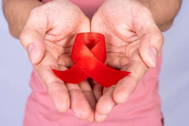 Nastro rosso di consapevolezza dell'aids che tiene a mano.