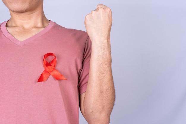 Nastro rosso di sensibilizzazione sull'aids sul petto dell'uomo e alza la mano per combatterli.