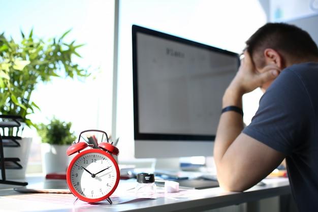 Supporto rosso della sveglia al tavolo da lavoro con l'uomo premuroso