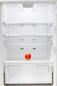 Mela rossa in un frigorifero vuoto.