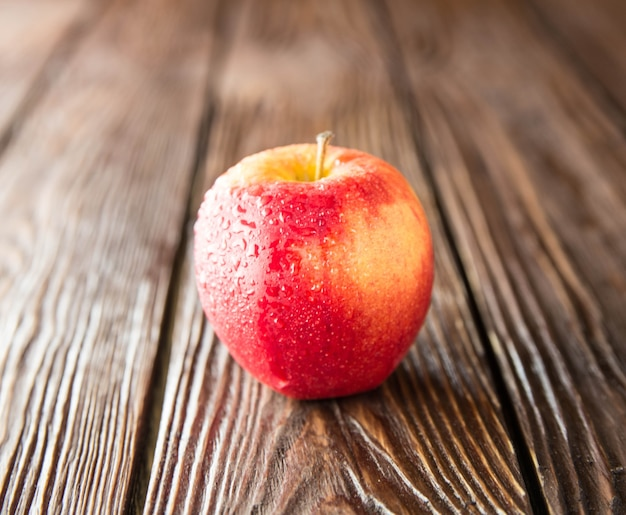 Mela rossa isolata sulla vecchia tavola di legno