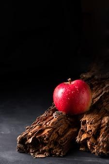 Mela rossa su una vecchia tavola di legno