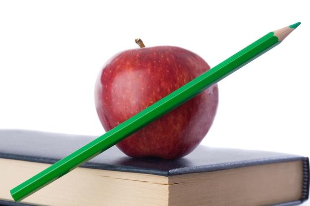 Una mela rossa con la matita verde in cima a molti libri su uno sfondo bianco