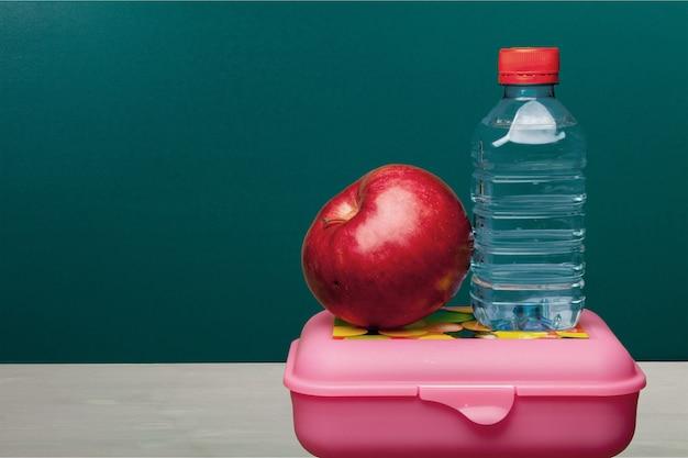 Mela rossa con acqua e cibo sul banco di scuola