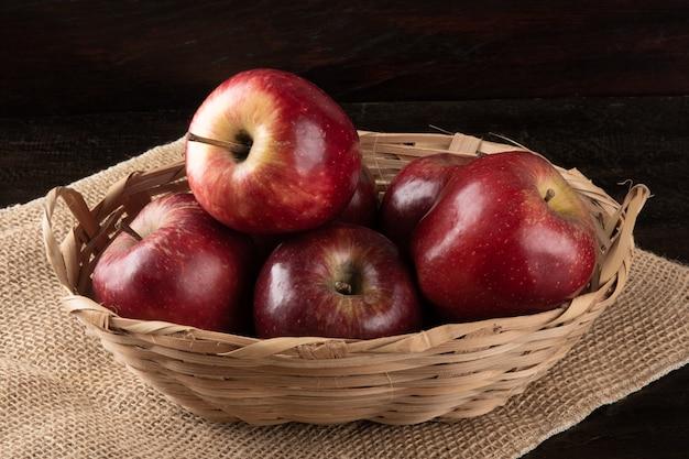 Merce nel carrello delle mele rosse con legno.