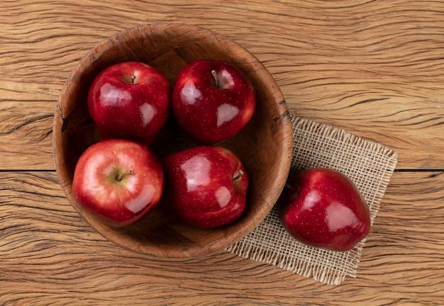 Mele rosse in una ciotola sul tavolo di legno.