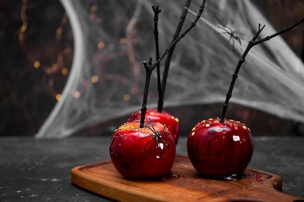 Mele rosse in caramello con un decoro di halloween festivo un trattamento originale per un halloween festivo