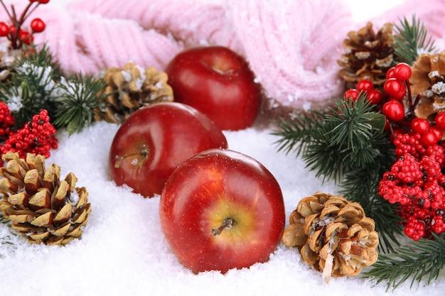 Mele rosse con rami di abete e sciarpa lavorata a maglia nella neve da vicino