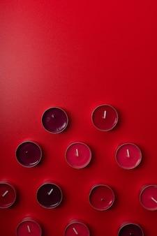 Candele aromatiche rosse su fondo rosso