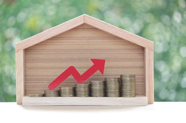 Grafico freccia rossa sulla pila di monete denaro in casa modello su sfondo verde naturale