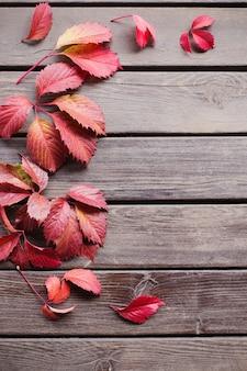 Foglie autunnali rosse su fondo di legno vecchio