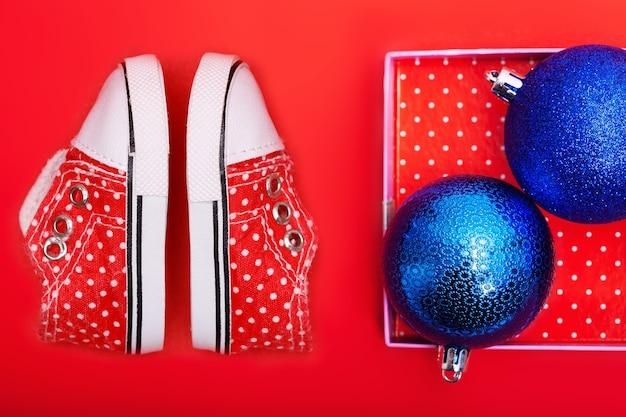 Scarpe da bambino rosse con pois bianchi su sfondo rosso con regali