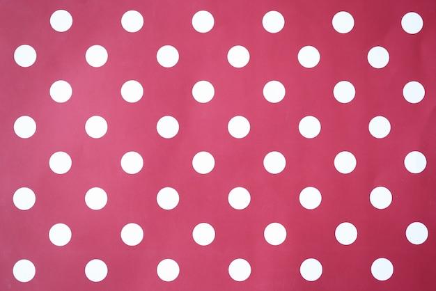 Sfondo rosso con cerchi bianchi a pois closeup