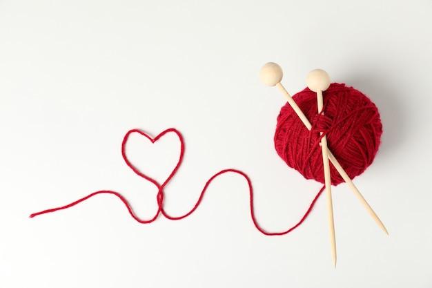 Gomitolo di lana rosso e ferri da maglia su sfondo bianco
