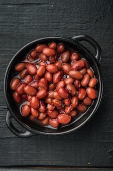 Fagiolo rosso, cibo in scatola, su sfondo di tavolo in legno nero, vista dall'alto piatta