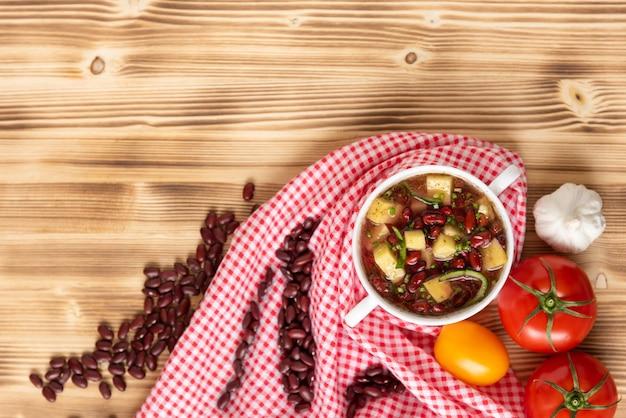 Zuppa di fagioli rossi con patate, pomodori e paprika in una ciotola di ceramica. vista dall'alto.