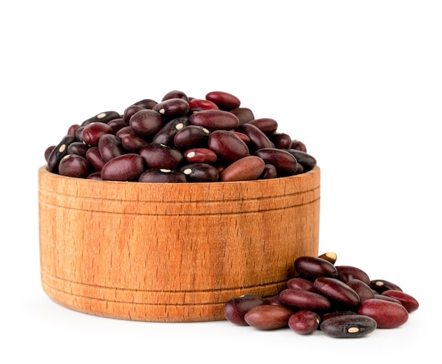 Fagioli rossi nel piatto di legno isolato