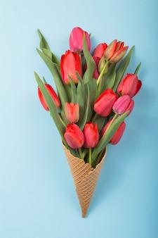 Bei tulipani rossi in un cono di cialda del gelato con la carta womans day su un fondo concreto. idea concettuale di un regalo floreale. umore primaverile