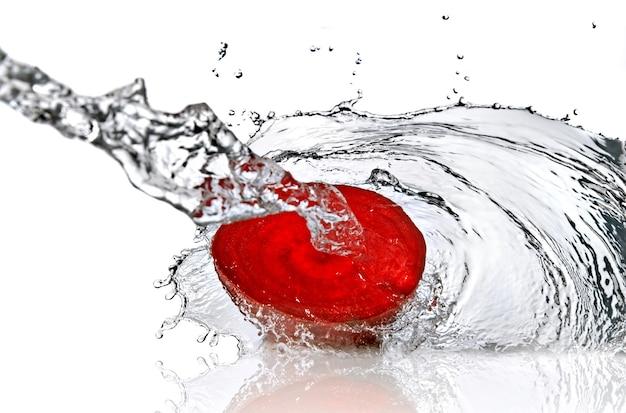 Barbabietola rossa con spruzzi d'acqua isolato su bianco