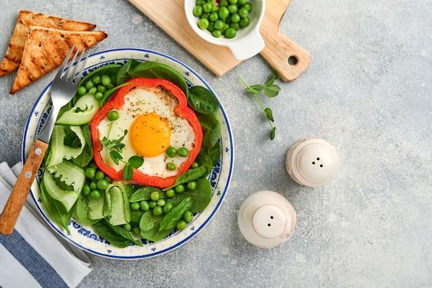 Peperoni rossi ripieni di uova, foglie di spinaci, piselli e microgreens su un piatto da colazione su sfondo grigio chiaro. vista dall'alto.