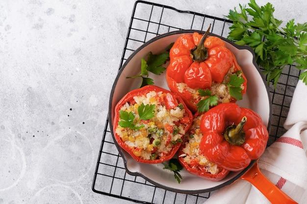 Peperoni rossi ripieni di riso e verdure in padella in ghisa su sfondo grigio cemento.