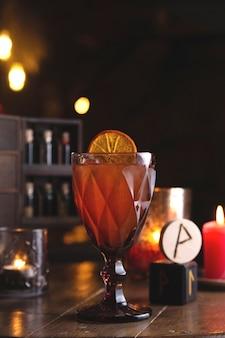 Cocktail a bacca rossa con decoro limone, tra rune e candele